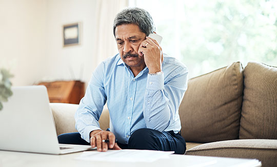 Senior man using phone and laptop in his living room.