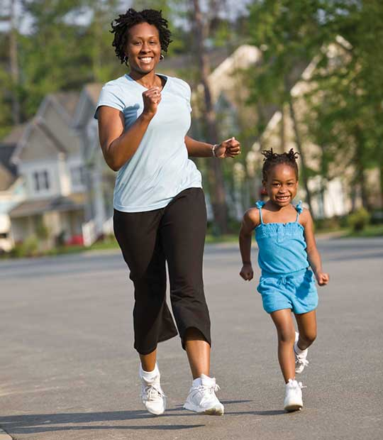 African-American woman jogging with daughter