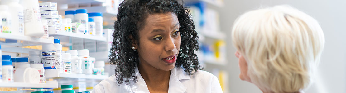 Female pharmacist talking with senior female while standing in front of shelves of pill bottles.